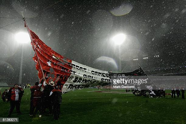 The Saints banner rips in half as rain and wind lash the ground before the AFL Second Semi final match between the St Kilda Saints and the Sydney...