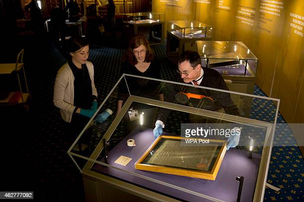 The Salisbury Cathedral 1215 copy of the Magna Carta is installed in a cabinet by Chris Woods, right, the director of the National Conservation...