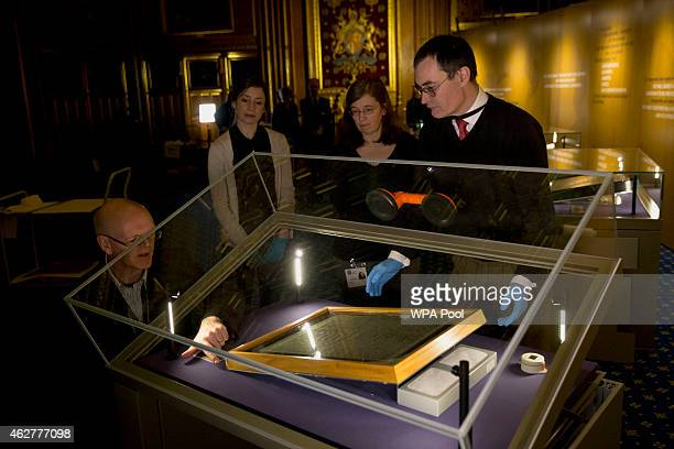 The Salisbury Cathedral 1215 copy of the Magna Carta is installed in a cabinet by Chris Woods right the director of the National Conservation Service...