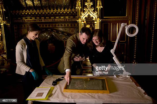 The Salisbury Cathedral 1215 copy of the Magna Carta is looked at by from left Parliamentary archive conservator Oriana Calman Chris Woods the...