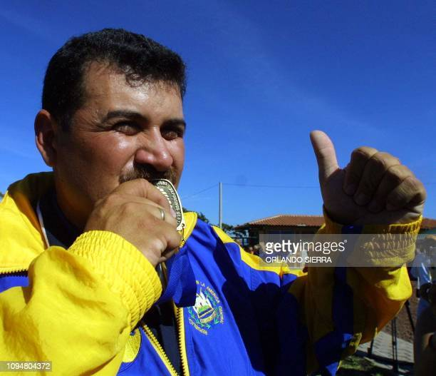 The Salvadorean Jorge Jimenez kisses 27 November 2002 in Merliot El Salvador the gold medal he won in the men's archery competition of 90 mts in the...