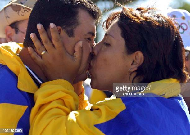 The Salvadorean Jorge Jimenez kisses his wife Patricia Najarro 27 November 2002 in Merliot El Salvador after winning the gold medal in the men's...