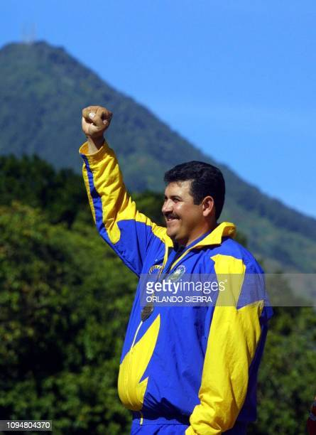 The Salvadorean Jorge Jimenez lifts his hand upcelebrating 27 November 2002 in Merliot El Salvador his gold medal in the men's archery competition of...