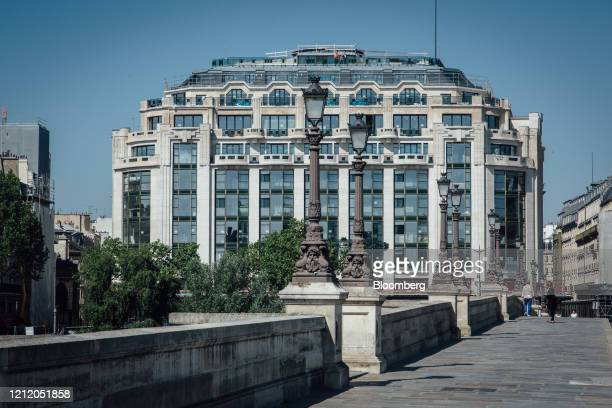 The Samaritaine luxury department store building operated by LVMH Moet Hennessy Louis Vuitton stands beside the Pont Neuf bridge in Paris France on...