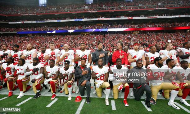 The San Francisco 49ers kneel and stand in solidarity on the sideline during the anthem prior to the game against the Arizona Cardinals at the...