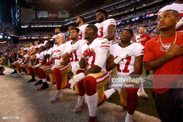 The San Francisco 49ers kneel and stand together during the anthem prior to the game against the Indianapolis Colts at Lucas Oil Stadium on October 8...