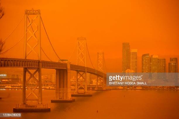 The San Francisco Bay Bridge and city skyline are obscured in orange smoke and haze as their seen from Treasure Island in San Francisco, California...