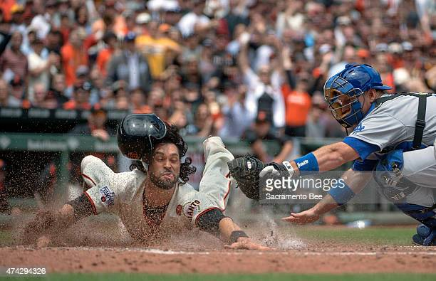 The San Francisco Giants' Angel Pagan dives to score past the tag attempt made by Los Angeles Dodgers catcher AJ Ellis in the third inning on...