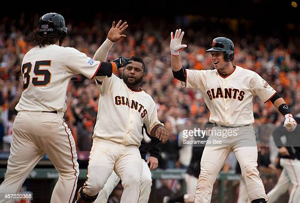 The San Francisco Giants' Brandon Crawford Buster Posey right and Pablo Sandoval celebrate at home after Gregor Blanco bunted Crawford home in the...