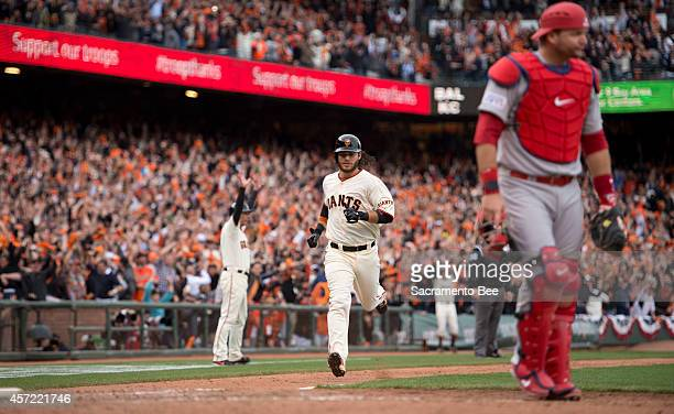 The San Francisco Giants' Brandon Crawford middle scores the wining run in the 10th inning as St Louis Cardinals catcher AJ Pierzynski right walks...