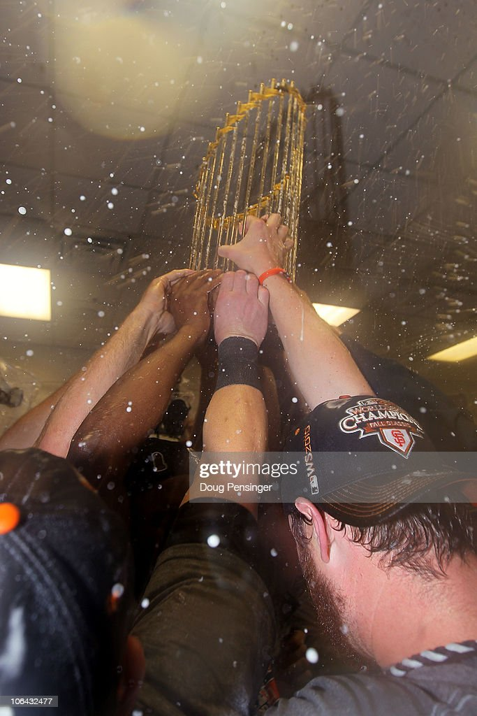The San Francisco Giants celebrate with the World Series trophy in the locker room after they won 3-1 against the Texas Rangers in Game Five of the 2010 MLB World Series at Rangers Ballpark in Arlington on November 1, 2010 in Arlington, Texas.