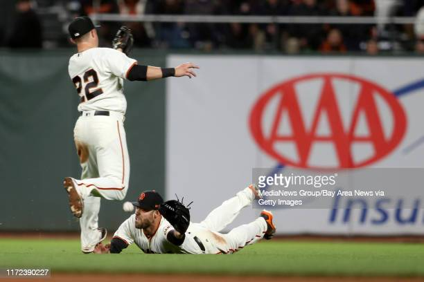 The San Francisco Giants' Christian Arroyo and Mac Williamson can't catch a base hit by the Los Angeles Dodgers' Justin Turner in the eighth inning...