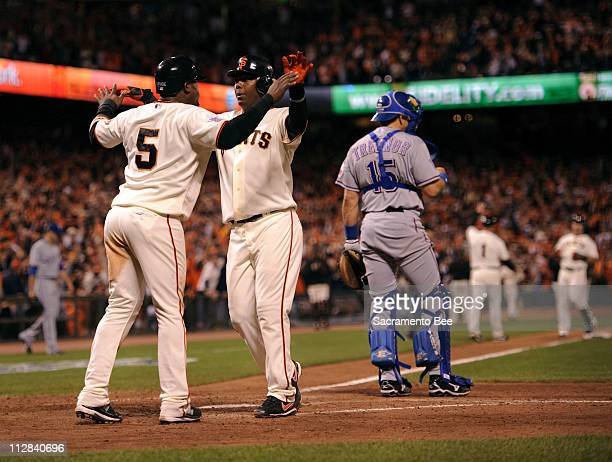 The San Francisco Giants' Juan Uribe and Edgar Renteria embrace after scoring on teammates Aaron Rowand's pinchhit triple against the Texas Rangers...