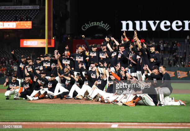 The San Francisco Giants pose for a team photo on the field after they clinched a playoff birth by beating the San Diego Padres at Oracle Park on...