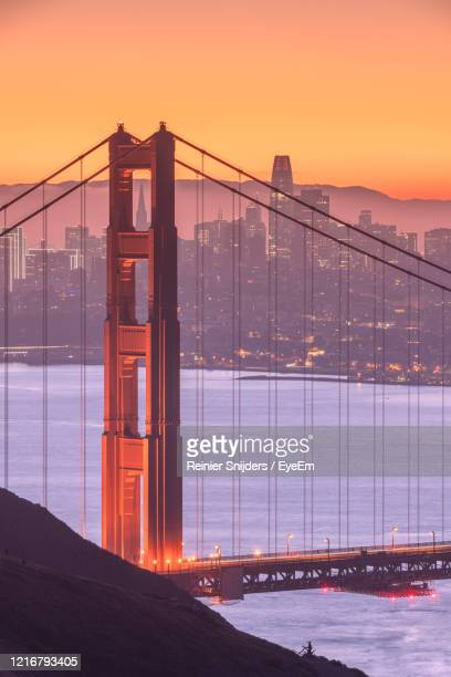 the san francisco skyline behind the golden gate bridge at sunset - golden hour stock pictures, royalty-free photos & images