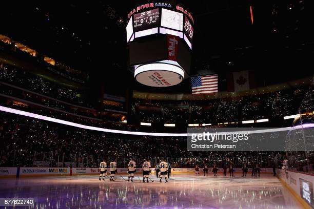 The San Jose Sharks and the Arizona Coyotes stand attended for the national anthem before the NHL game at Gila River Arena on November 22 2017 in...