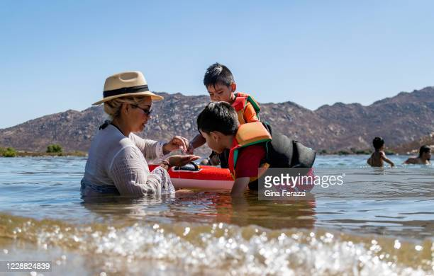The Sanchez family of Anaheim searches for small pebbles while cooling off in the 105 degree temperature at Lake Perris State Recreation Area on...