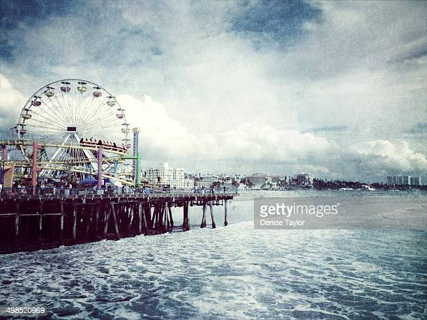 The Santa Monica pier and ferris wheel along the shore on a stormy winter day.