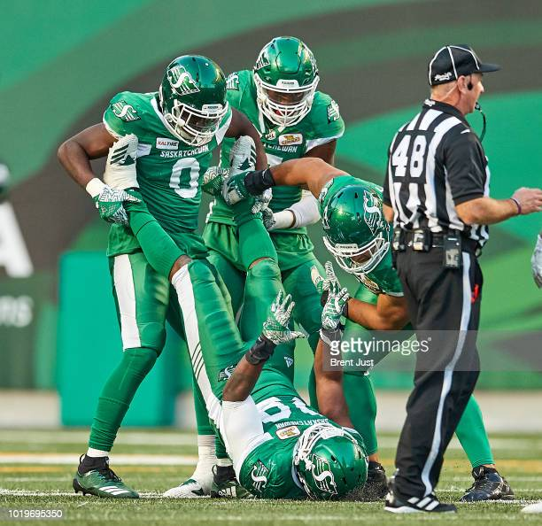 The Saskatchewan Roughrider defensive line celebrates after Charleston Hughes made a sack in the game between the Calgary Stampeders and Saskatchewan...