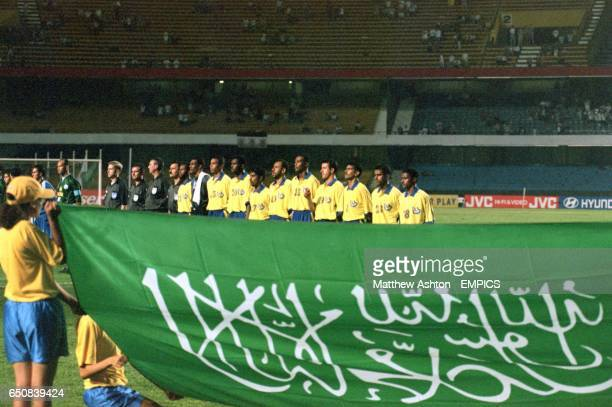The Saudi Arabian flag is held up as the Al Nassr team stand for their national anthem