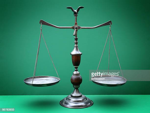 The scales of justice against a green background