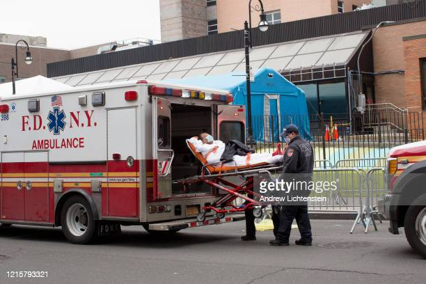 The scene outside of Elmhurst Hospital's trauma unit remains busy with ambulances frequently leaving and arriving dropping off patients many who are...