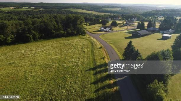 Die Landschaft Luftaufnahme des Poconos, Monroe County, Pennsylvania. Die sonnigen Sommermorgen. Die Panorama Überblick über das Feld und Wald auf den Kunkletown, dann auf die kleine Farm in der Nähe von der Straße.