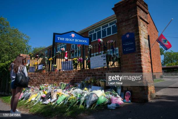 The school flag flies at half mast as a student lays flowers and pays respects to the murdered school teacher James Furlong outside The Holt School...