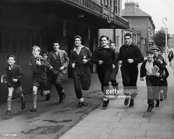 The schoolboy fans have fun running in the streets around Highbury Stadium with members of the Arsenal football team Wilkins David Bowen and Cliff...