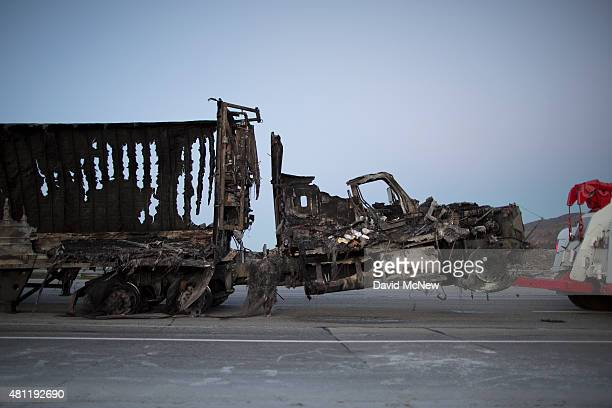 The scorched remains of a truck are towed at the North Fire which caused people to abandon their vehicles and flee as flames jumped the 215 freeway...
