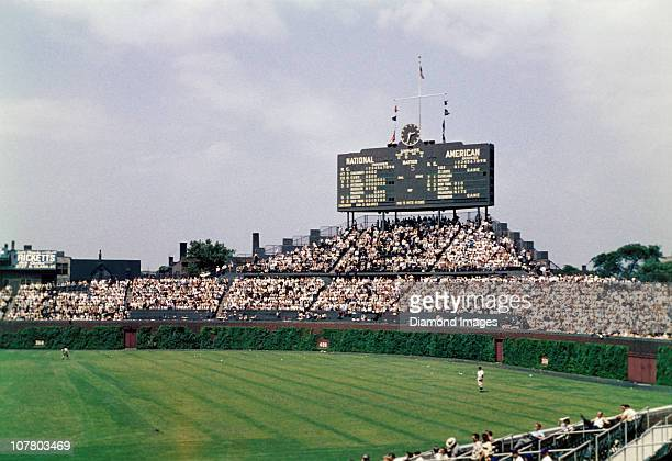 The scoreboard above the centerfield bleachers gives the score of the moment for this game and those around Major League Baseball prior to the top of...
