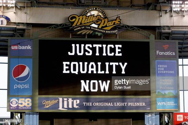 """The scoreboard displays a message of """"Justice Equality Now"""" before the game between the Cincinnati Reds and Milwaukee Brewers at Miller Park on..."""