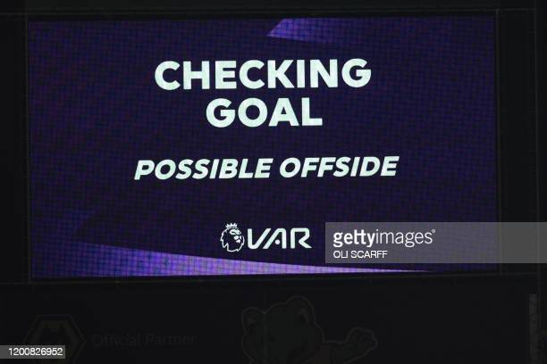 The scoreboard shows the VAR is reviewing a goal scored by Wolverhampton Wanderers' French defender Willy Boly for a possible offside during the...