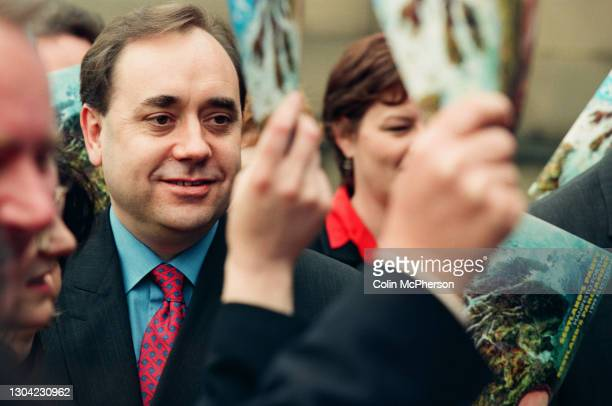 The Scottish National Party leader Alex Salmond poses for photographs with a copy of the SNP's 1999 Scottish Parliament elections at the former Royal...