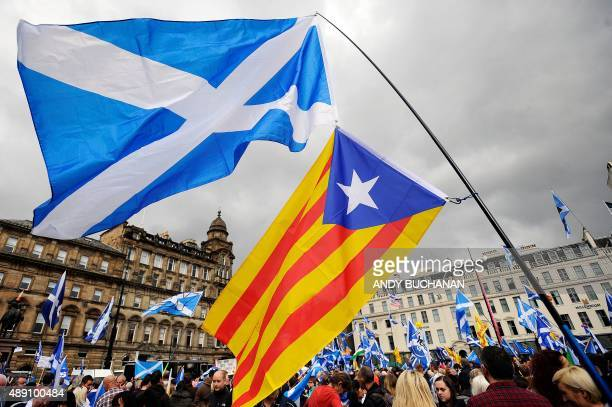 The Scottish Saltire and the nationalist flag of Catalonia are pictured as Scottish pro independence supporters hold a rally in George Square in...