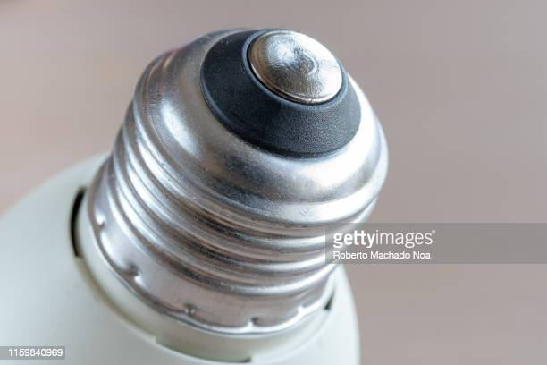 The screw threads part of a compact fluorescent light bulb Close up image