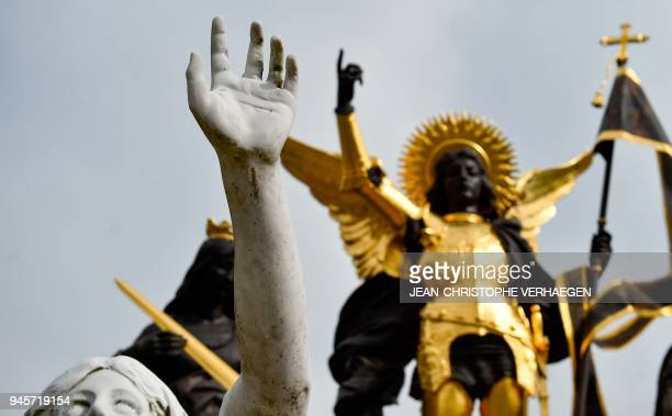 The sculpture 'Jeanne d'Arc and her voices' is pictured in front of BoisChenu's basilica dedicated to Jeanne d'Arc on April 12 2018 in...