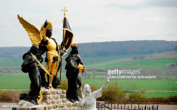 The sculpture 'Jeanne d'Arc and his voices' is pictured in front of BoisChenu's basilica dedicated to Jeanne d'Arc on April 12 2018 in...