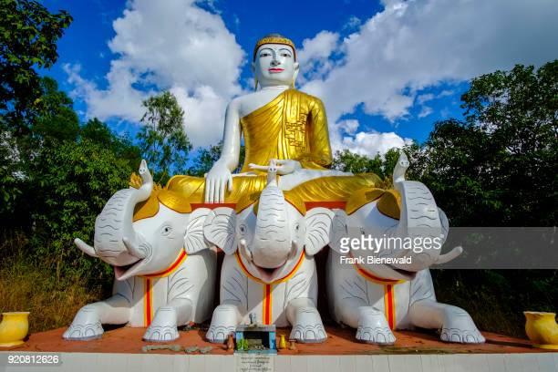 The sculpture of Buddha sitting on three white elephants is located below Laykyun Sekkya Buddha in Maha Bodhi Ta Htaung near Khatakan Taung village