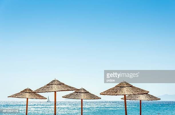 the sea and parasols at the beach - greece stock pictures, royalty-free photos & images