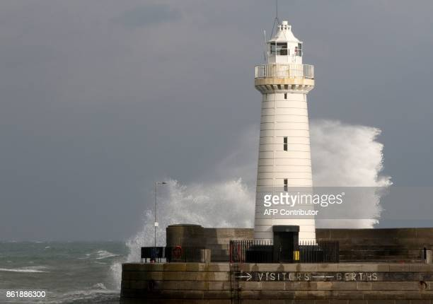 TOPSHOT The sea breaks over the harbour behind Donaghadee lighthouse on the Irish Sea coast east of Belfast in Northern Ireland on October 16 2017 as...