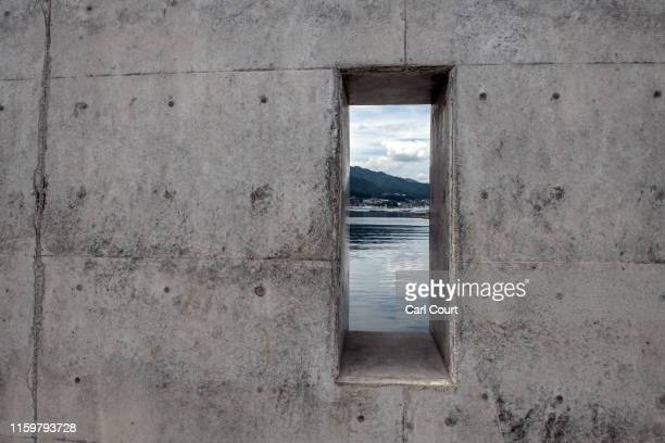 The sea is seen through a hole in a newlybuilt concrete seawall in a village near Ofunato one of the towns hit by the 2011 Tohoku earthquake and...
