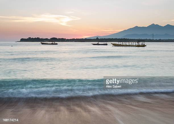 the sea laps up on the sand in gili trawangan at sunrise. - alex saberi photos et images de collection