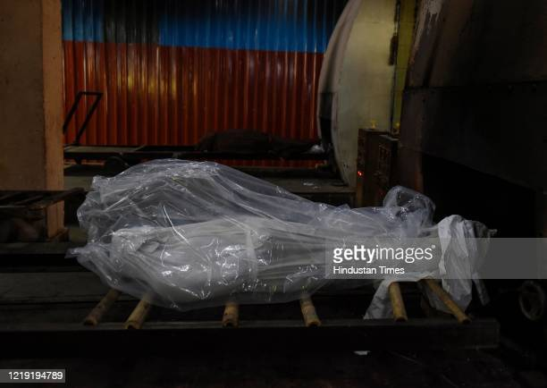 The sealed body of a person who died due to coronavirus is placed at the mouth of a furnace before cremation at Nigambodh Ghat crematorium, on June...