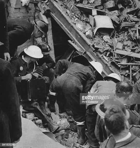 The search goes on' 1941 'Throughout the night and all next day wardens rescue men and ambulance men burowed into the wreckage of this house looking...