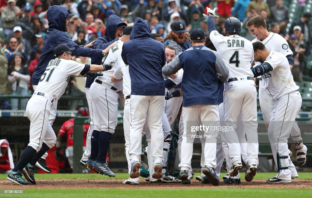 The Seattle Mariners celebrate after the game winning two run home run by Mitch Haniger #17 of the Seattle Mariners in the ninth inning against the Los Angeles Angels of Anaheim during their game at Safeco Field on June 13, 2018 in Seattle, Washington.