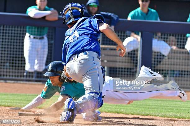 The Seattle Mariners' Joey Wong scores past Kansas City Royals catcher Drew Butera in the seventh inning during spring training in Peoria Ariz on...