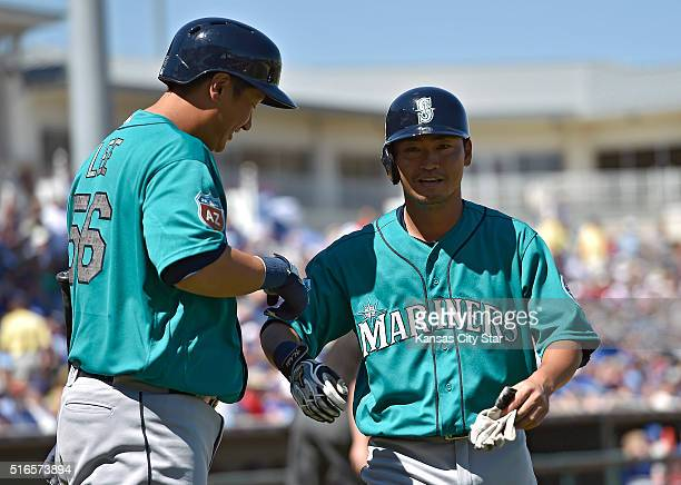 The Seattle Mariners' Nori Aoki right is greeted by Dae Ho Lee after scoring on a single by Kyle Seager in the first inning against the Kansas City...