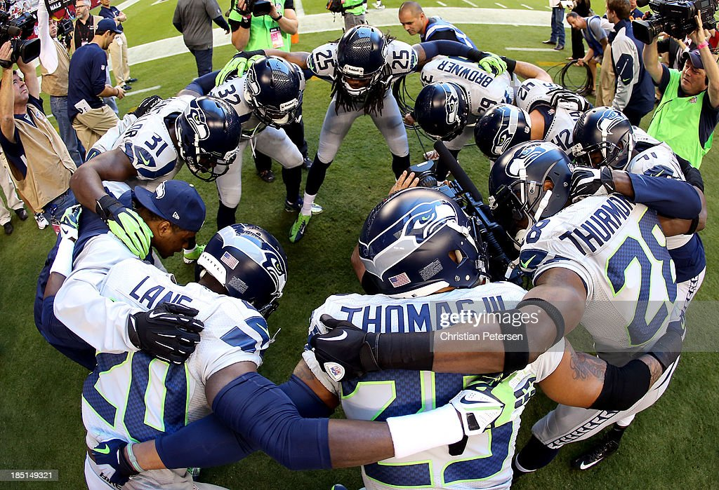 The Seattle Seahawks huddle before a game against the Arizona Cardinals at the University of Phoenix Stadium on October 17, 2013 in Glendale, Arizona.