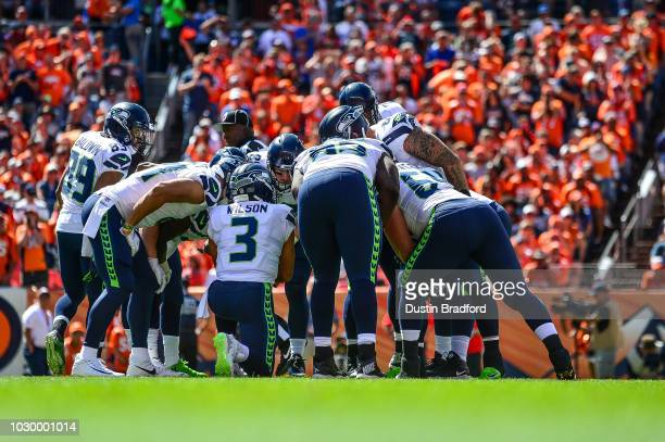 The Seattle Seahawks offense huddles around quarterback Russell Wilson in the first quarter of a game against the Denver Broncos at Broncos Stadium...